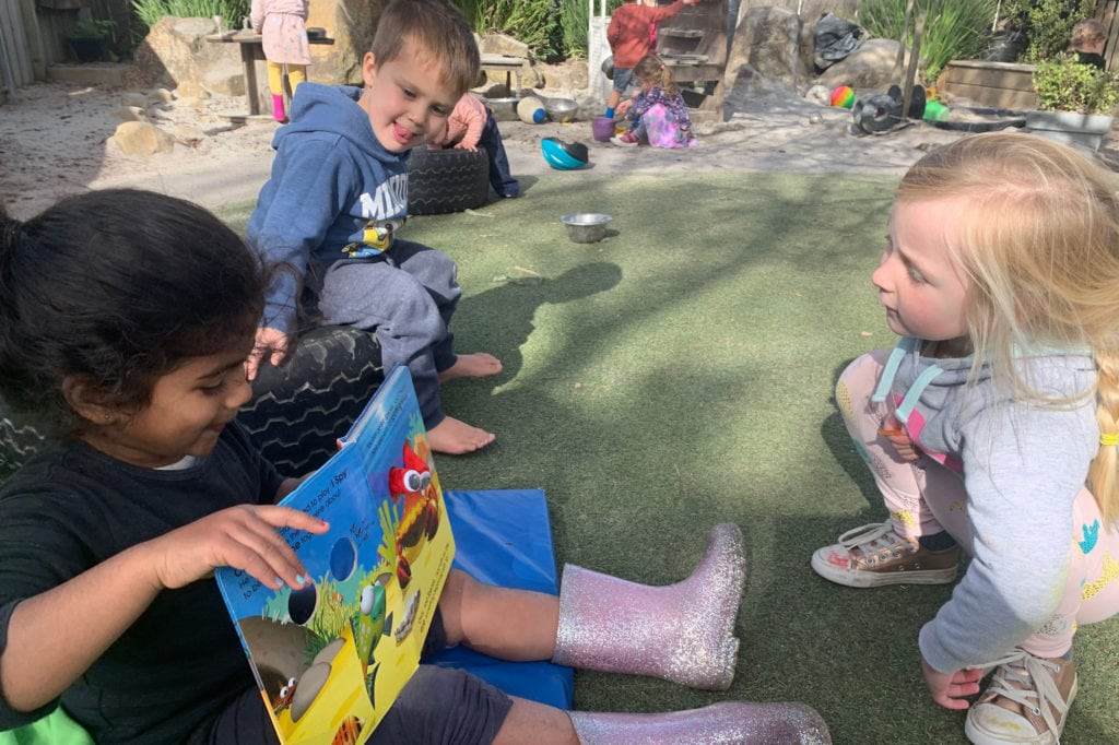 Children reading a book outside Early Learning Centre